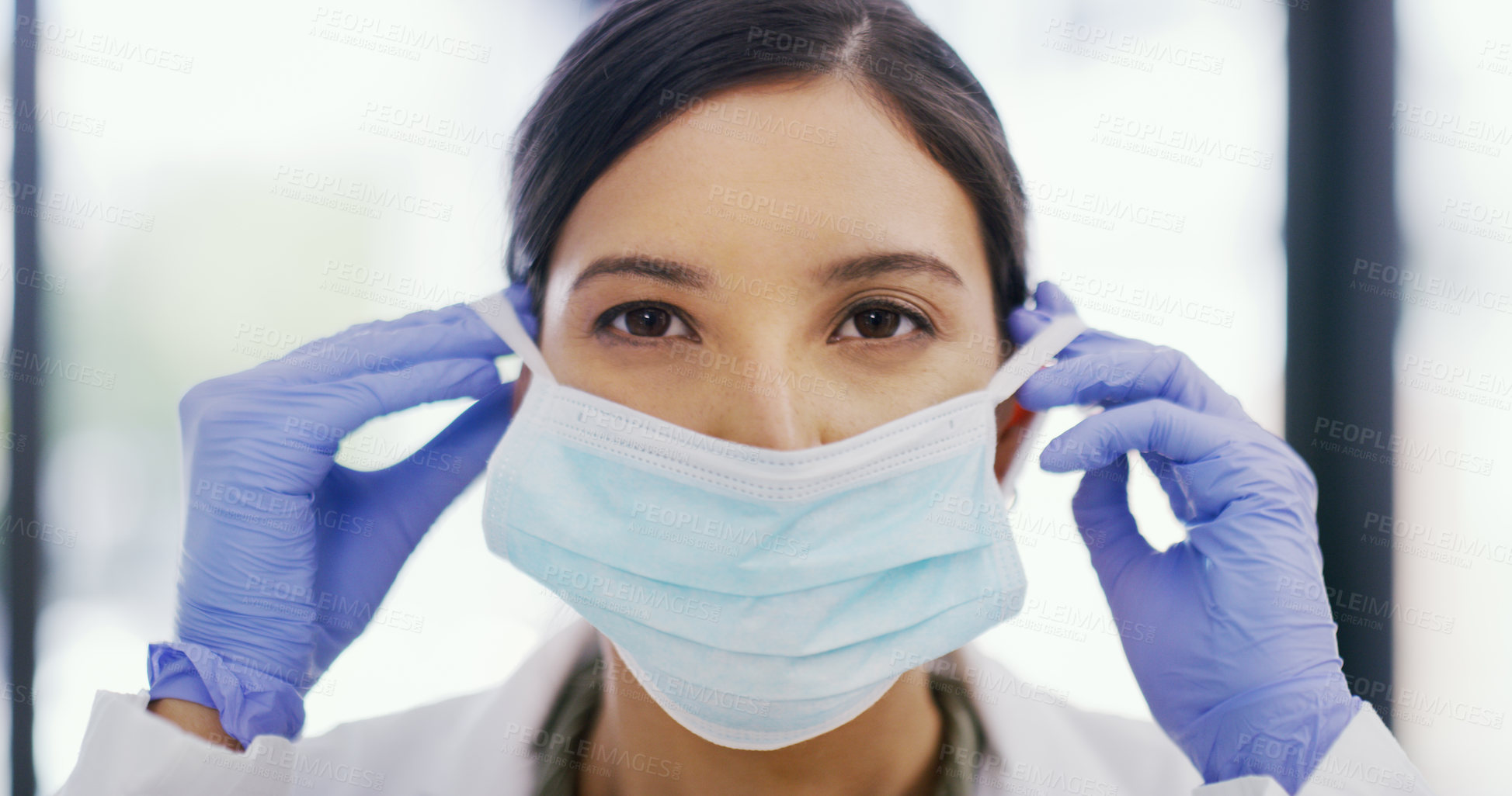 Buy stock photo Portrait of a female doctor putting her mask on