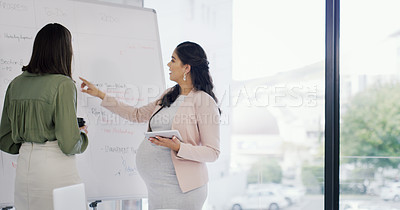 Buy stock photo Shot of two businesswomen having a discussion in the boardroom
