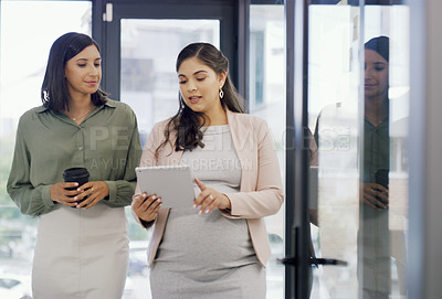 Buy stock photo Shot of two businesswomen discussing something on a digital tablet