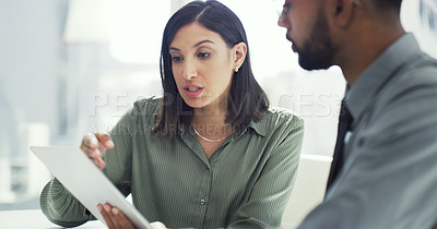 Buy stock photo Cropped shot of two businesspeople having a discussion while using a digital tablet