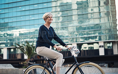 Buy stock photo Shot of a mature businesswoman traveling with a bicycle through the city