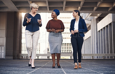 Buy stock photo Shot of a group of businesswomen having a discussion against a city background