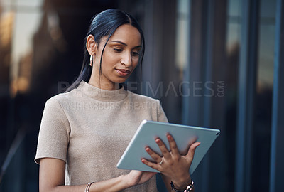 Buy stock photo Cropped shot of an attractive young businesswoman using her tablet while working in the office