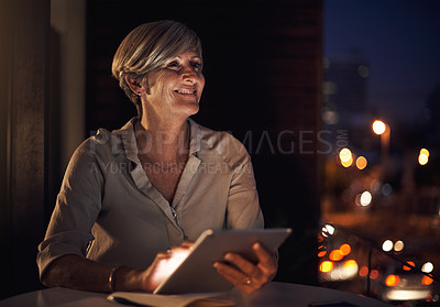 Buy stock photo Cropped shot of an attractive mature businesswoman using her tablet while working late in the office