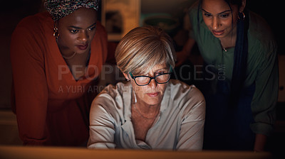 Buy stock photo Shot of a group of businesswomen working together on a computer in an office at night