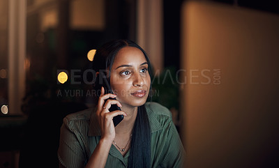 Buy stock photo Shot of a young businesswoman talking on a cellphone while using a computer in an office at night