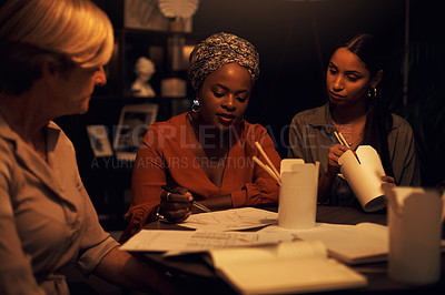 Buy stock photo Shot of a group of businesswomen eating takeout while working together in an office at night