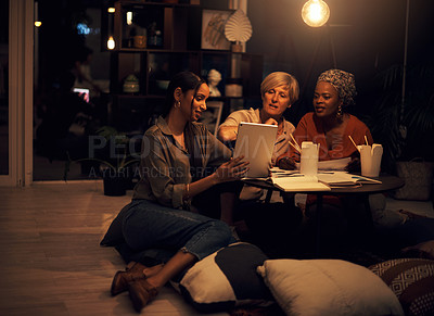 Buy stock photo Shot of a group of businesswomen working together on a digital tablet in an office at night