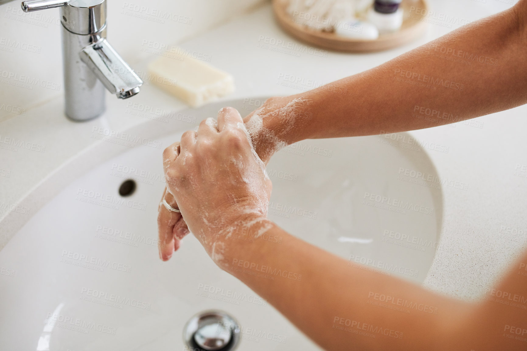 Buy stock photo Cropped shot of a woman washing her hands with soap in the bathroom sink at home