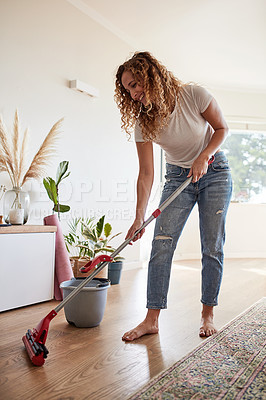 Buy stock photo Shot of a young woman mopping the floor at home