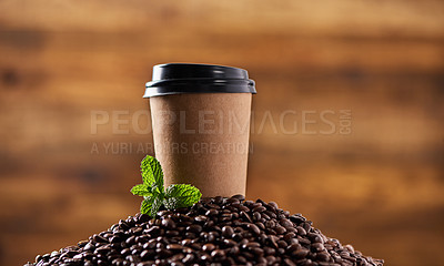 Buy stock photo Closeup shot of a mint leaf and a paper cup on a pile of coffee beans