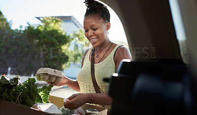 Buy stock photo Shot of a young woman packing groceries into the trunk of her car