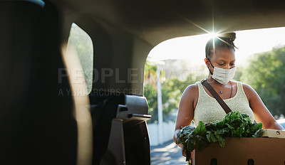 Buy stock photo Shot of a young woman wearing a mask and packing groceries into the trunk of her car