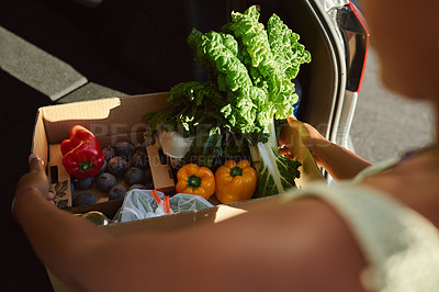 Buy stock photo Shot of a woman packing groceries into the trunk of her car