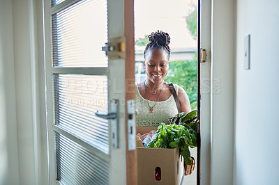 Buy stock photo Shot of a young woman returning home from buying groceries
