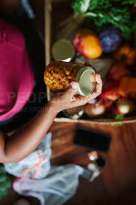 Buy stock photo High angle shot of a woman unpacking her groceries in the kitchen at home