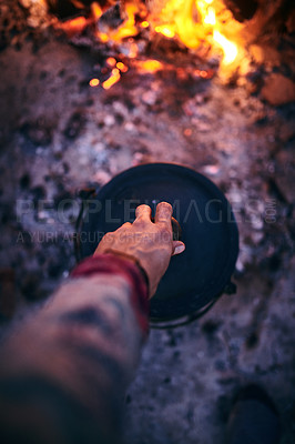 Buy stock photo Cropped shot of a man cooking traditional South African food by campfire outdoors