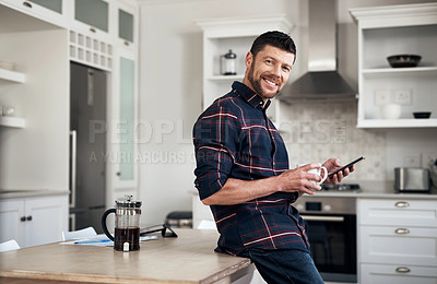 Buy stock photo Shot of a young man using a smartphone and having coffee in his kitchen at home