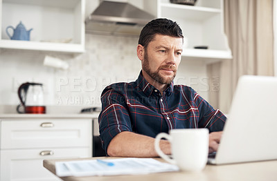 Buy stock photo Shot of a young man using a laptop while going over his finances at home