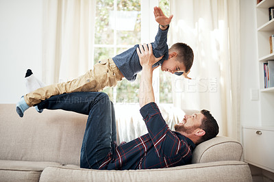 Buy stock photo Shot of a happy little boy having fun with his father on the sofa at home
