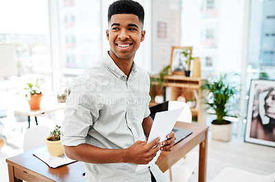 Buy stock photo Shot of a confident young businessman going over paperwork in a modern office
