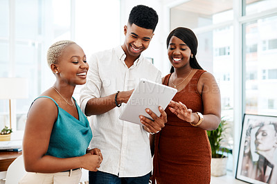 Buy stock photo Shot of a group of young businesspeople using a digital tablet together in a modern office