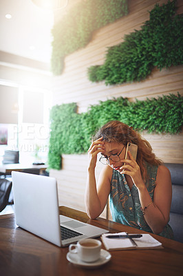 Buy stock photo Shot of a young woman looking stressed using a laptop and smartphone while working at a cafe