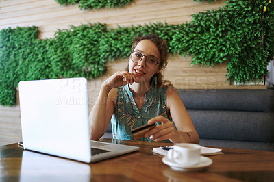 Buy stock photo Shot of a young woman using a laptop and credit card while working at a cafe