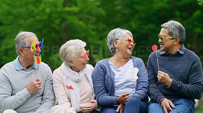 Buy stock photo Shot of a group of happy senior men and women wearing fun glasses at the park