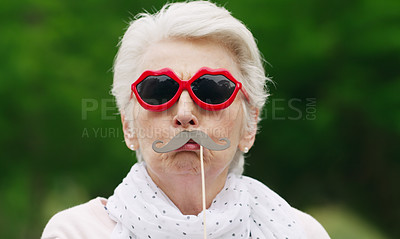 Buy stock photo Portrait of a senior woman wearing fun glasses at the park