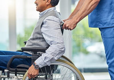 Buy stock photo Shot of a nurse helping a senior man in a wheelchair