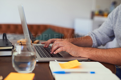 Buy stock photo Closeup shot of an unrecognisable man working on a laptop at home