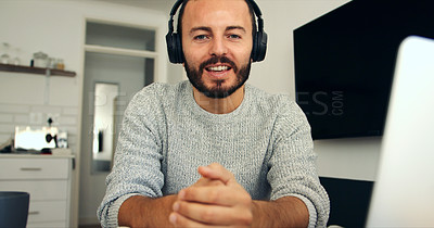 Buy stock photo Portrait of a young man wearing headphones while using a laptop at home