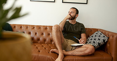 Buy stock photo Shot of a young man looking thoughtful while writing in a book at home