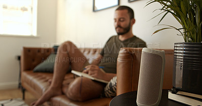 Buy stock photo Shot of a wireless speaker with a man sitting in the background at home