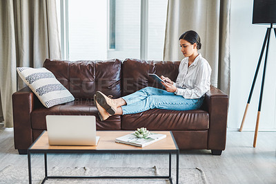 Buy stock photo Shot of a young woman using a digital tablet on the sofa while working from home