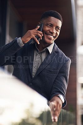 Buy stock photo Shot of a young businessman talking on a cellphone while standing on the balcony of an office