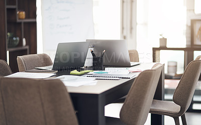 Buy stock photo Still life shot of laptops and paperwork on a table in a modern office