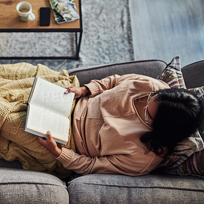 Buy stock photo High angle shot of a young woman reading a book on the sofa at home