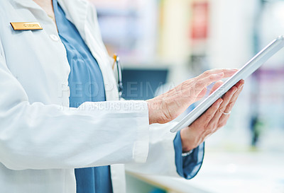 Buy stock photo Cropped shot of a woman using a digital tablet while working in a pharmacy