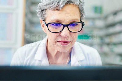 Buy stock photo Shot of a mature woman using a computer while working in a pharmacy