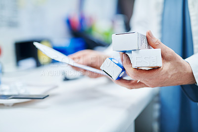 Buy stock photo Cropped shot of a pharmacist holding boxes of medication in a chemist
