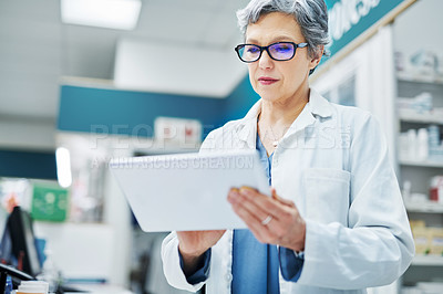 Buy stock photo Shot of a mature woman using a digital tablet while working in a pharmacy