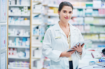 Buy stock photo Shot of a young woman using a digital tablet while working in a pharmacy