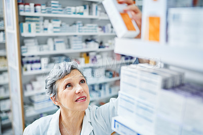 Buy stock photo Shot of a mature pharmacist reaching for a box of medication from the shelves in a chemist