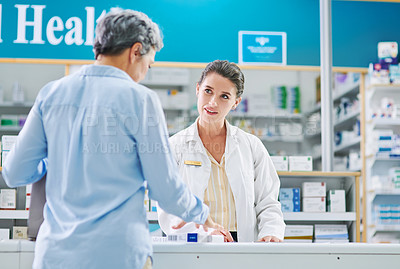 Buy stock photo Shot of a young pharmacist assisting a mature woman in a chemist