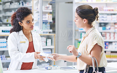 Buy stock photo Shot of a young pharmacist handing a customer a box of medication in a chemist
