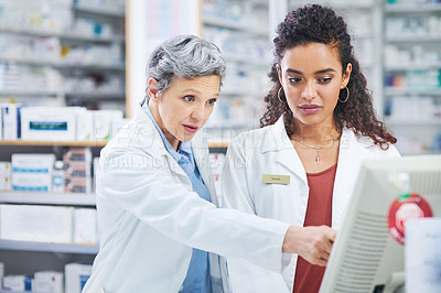 Buy stock photo Shot of two pharmacists using a computer in a chemist