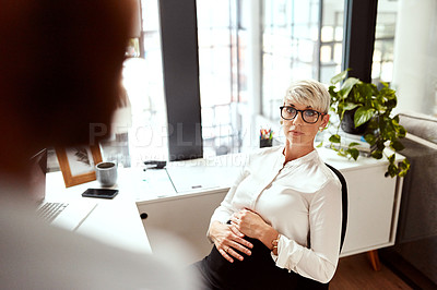 Buy stock photo Shot of a pregnant businesswoman talking to a colleague in an office