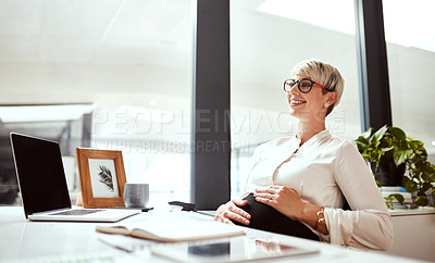 Buy stock photo Shot of a pregnant businesswoman sitting at a desk in an office